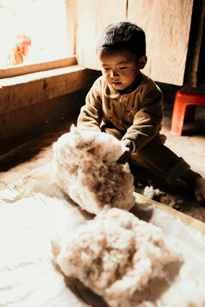 Trek au Laos enfant tribu akha joue avec laine