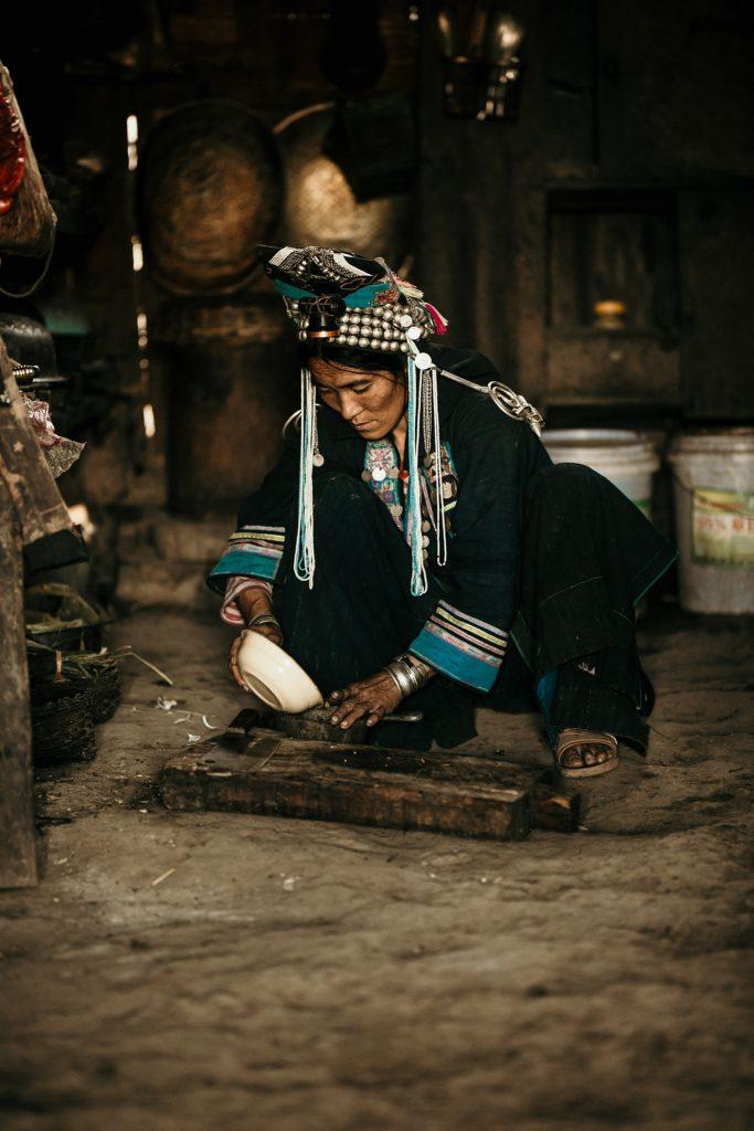 Trek au Laos chez les Akha femme prépare repas dans sa maison