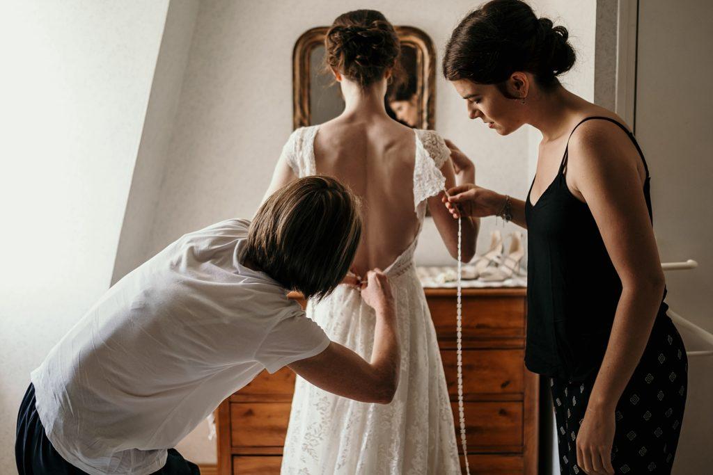 Photographe Mariage Bretagne mariée enfile sa robe