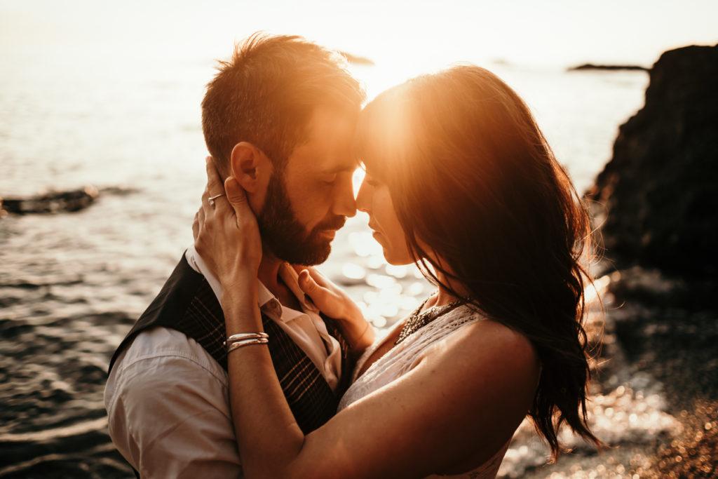 Séance couple sur la plage front contre front au coucher de soleil