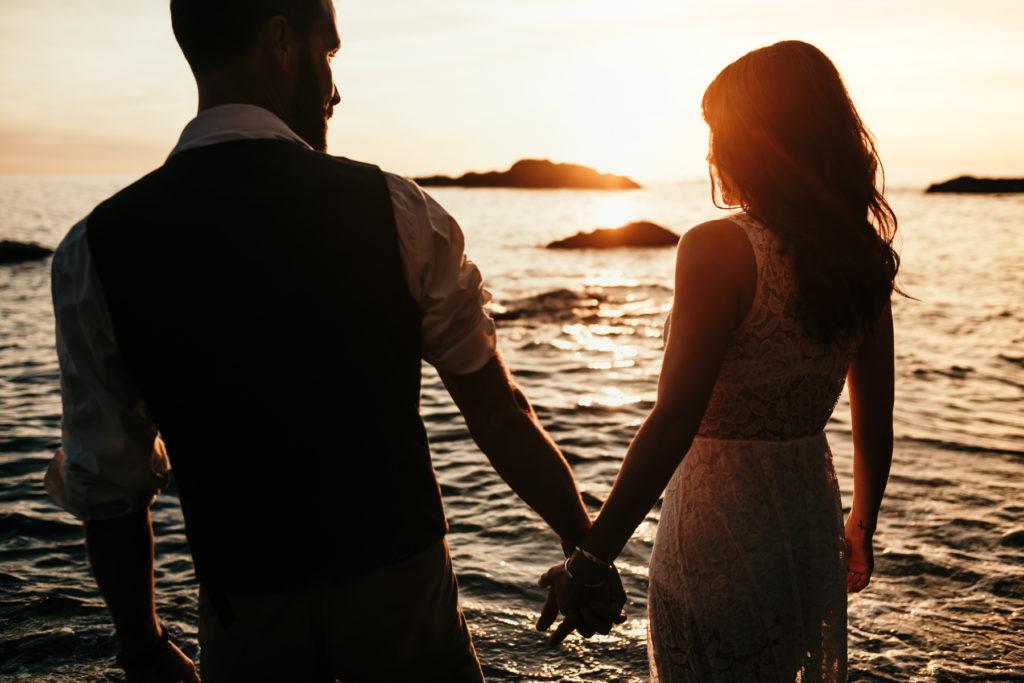 Séance couple sur la plage main dans la main au coucher de soleil