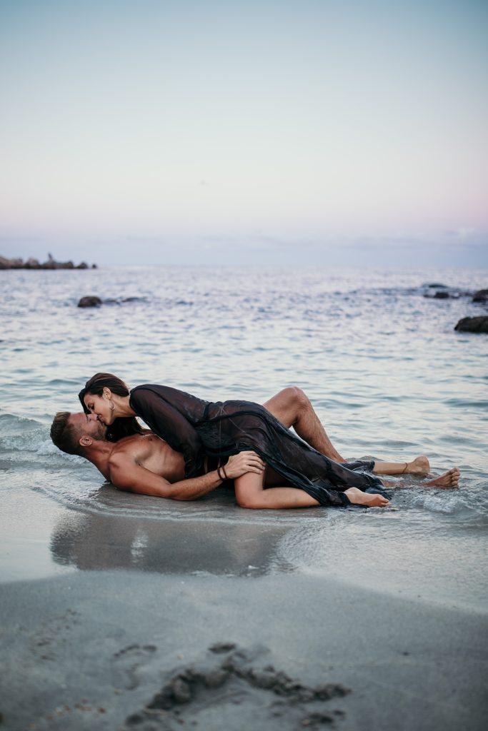 Shooting couple dans l'eau l'amour a la plage