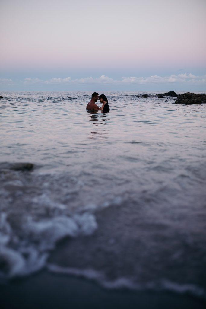 Shooting couple dans l'eau au coucher de soleil